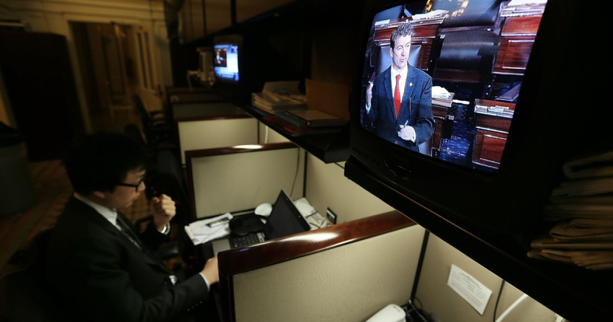 Sen. Rand Paul (R-KY) is seen on a TV monitor participating in a filibuster on the Senate floor as Politco reporter Tim Mak works on his story at the Senate Press Gallery March 6, 2013 on Capitol Hill in Washington, DC. Paul was filibustering the Senate to oppose the nomination of John Brennan to be the next director of CIA.</p>