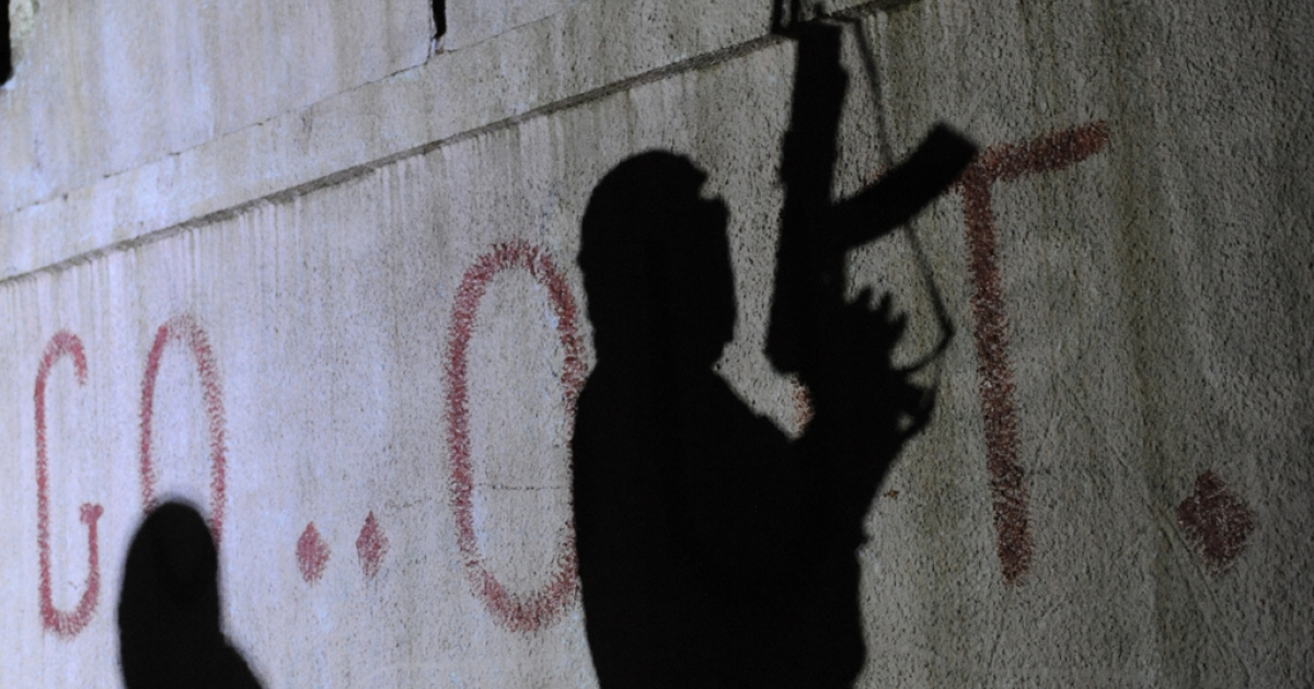 The shadows of armed Free Syrian Army rebels are seen on a wall at the entrance to the north Syrian city of Binnish on Feb. 15, 2012.</p>
