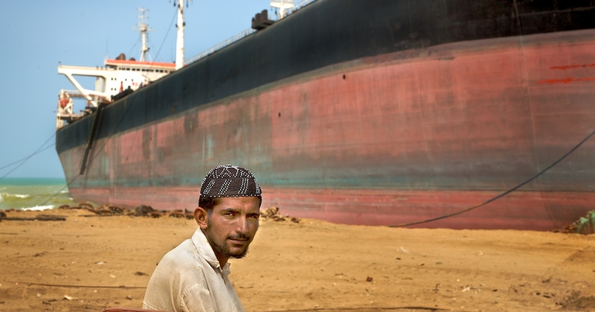 A watchman guards against the ship being dragged out to sea at high tides in Gaddani, Pakistan on May 31, 2008.</p>