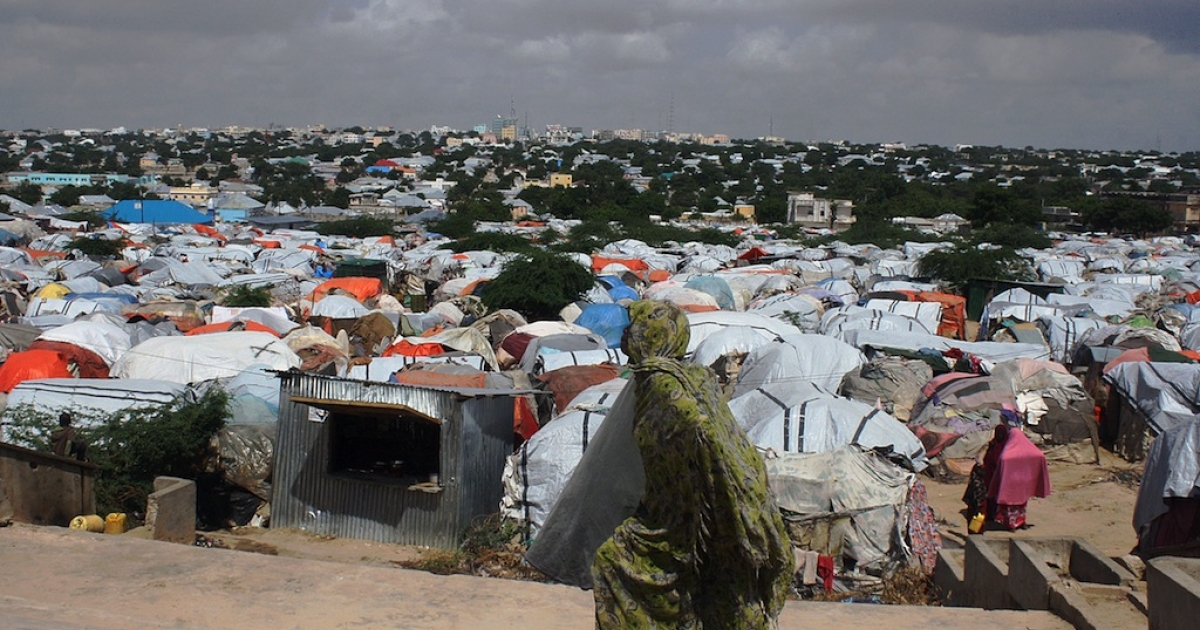 A Somali refugee walks in front of a camp for internally displaced people near the Parliament in Mogadishu on Dec. 4, 2012.</p>