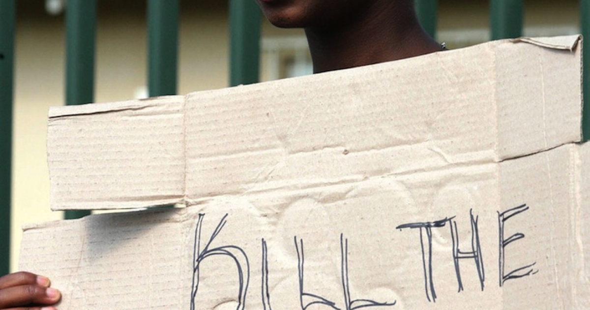 An angry resident of the South African informal settlement Skielik stands with a placard during a protest outside the Swartruggens Magistrate's Court, west of Johannesburg 17 January 2008.</p>