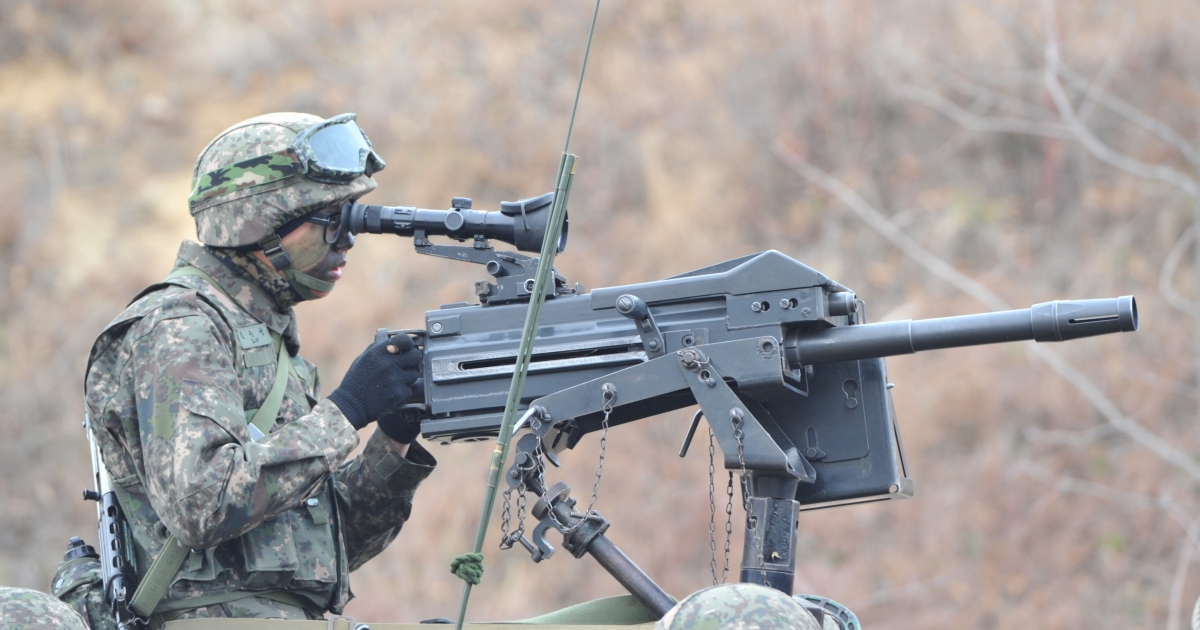 A South Korean soldier looks through the scope of a K-4 automatic grenade launcher at a check point during a drill near border in Paju on March 28.</p>