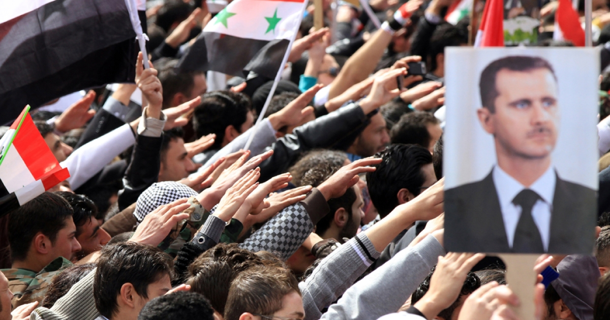 Syrians wave national flags and portraits of President Bashar al-Assad as they rally in support of the regime on the first anniversary of the anti-regime revolt in Damascus on March 15, 2012. Assad reshuffled the leadership of the Syrian Baath party on July 8, 2013 amid military gains against the rebels.</p>