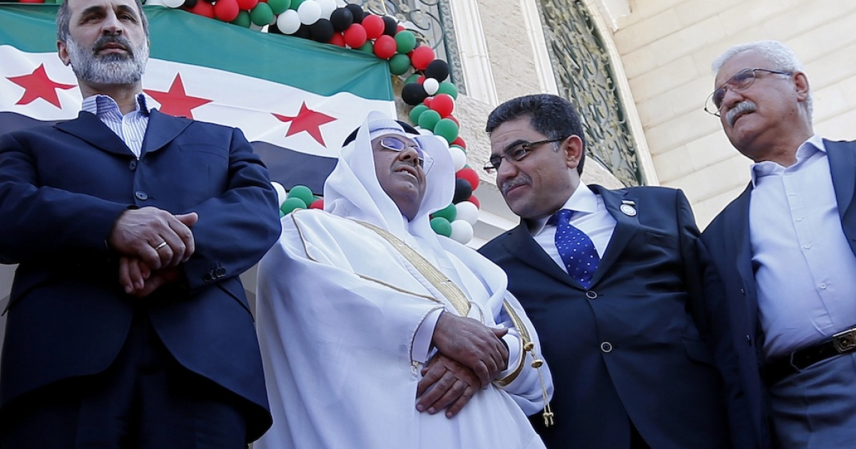 Prime Minister of the interim government of Syria Ghassan Hitto (2R), head of the Syrian opposition delegation, Ahmed Moaz al-Khatib (L), and Syrian National Council (SNC) President George Sabra (R) at the inauguration of the first Syrian interim government embassy in Doha on March 27, 2013.</p>