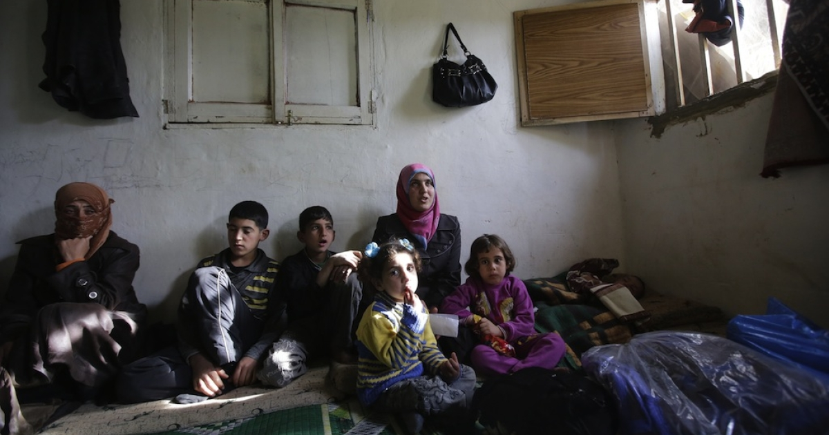 Bushra (C-top), who is the 1,000,000th registered Syrian refugee at the UNHCR, sits among children inside a shanty rented by her missing husband's family in a poor neighbourhood at the entrance of the northern Lebanese city of Tripoli on March 7, 2013. The number of Syrians who have fled their country since a deadly civil conflict erupted two years ago has hit one million, the UN's refugee agency said on March 6.</p>
