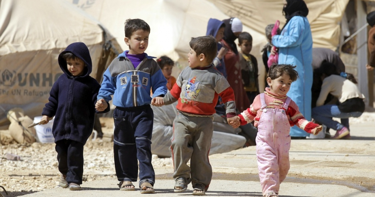 Syrian children walk amid tents at the Zaatari refugee camp, near the Syrian border with Jordan in Mafraq on March 7, 2013.</p>