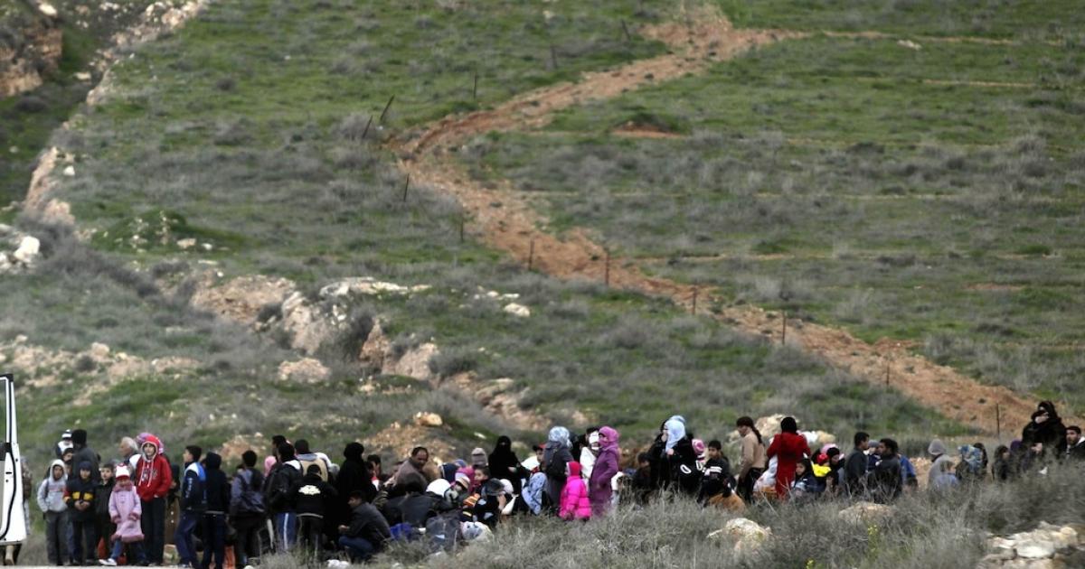 Syrian refugees cross the border from Syria into Jordan, near Mafraq, on Feb. 18, 2013.</p>