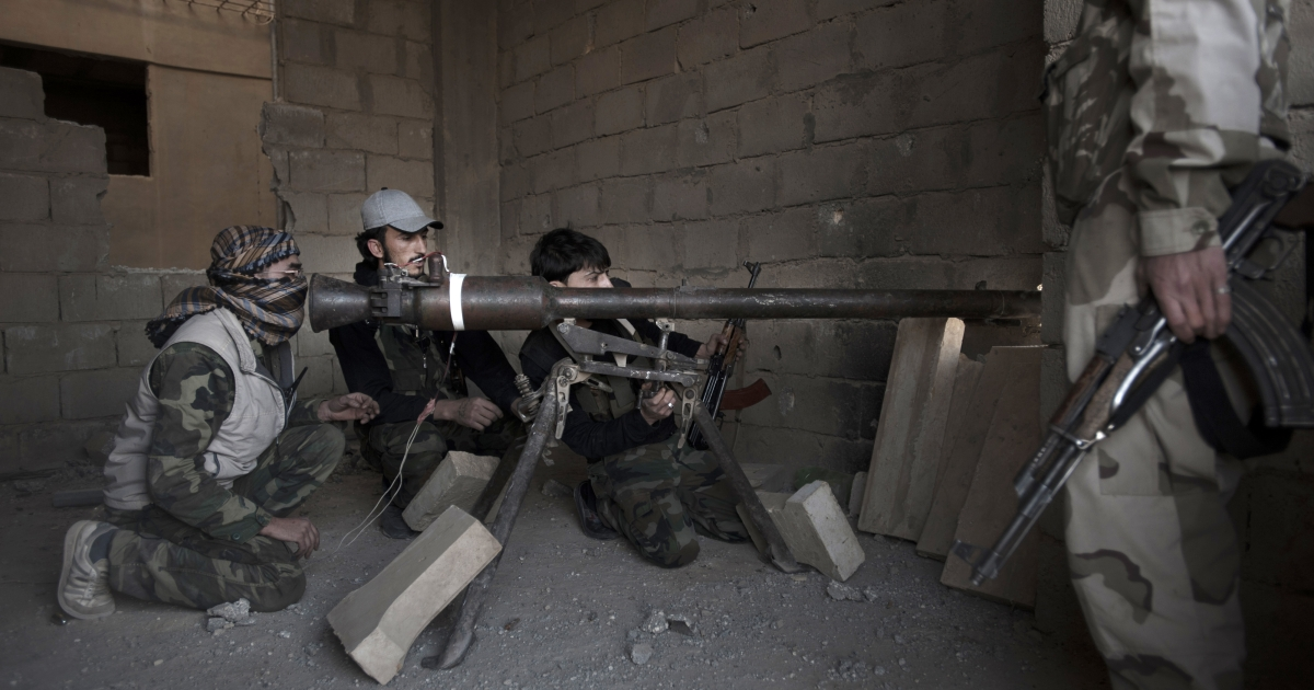 Rebels fighters prepare to fire a portable canon against an adjacent Syrian government-held building during fighting on February 27, 2013 in the Hawiqah neighbourhood of the eastern Syrian town of Deir Ezzor. Syria's opposition and foreign powers hold crucial talks in Rome with Washington suggesting it is ready to boost support to rebels in their struggle against President Bashar al-Assad.</p>