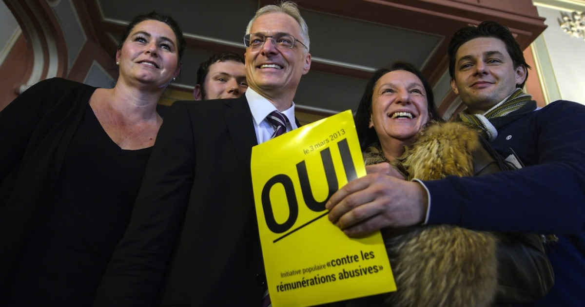 Swiss businessman and senator Thomas Minder (3rdR) poses on March 3, 2013 with members of the support committee behind a poster reading 'Yes' in French while waiting for the result of a nationwide vote in Schaffhausen. Switzerland took part in a popular vote on whether to rein in executive pay and force business leaders to give up departure compensation known as golden parachutes.</p>