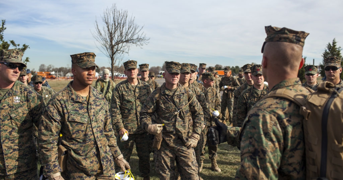 US Marines from the 26th Marine Expeditionary Unit and U.S. Navy seamen from the U.S.S. Wasp receive orders from a commanding officer (R) November 6, 2012.</p>