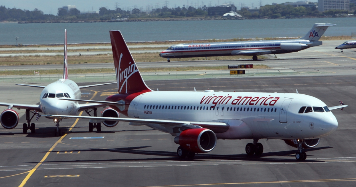 Two Virgin America planes taxi on the runway after arriving at San Francisco International Airport on Aug. 8, 2007, in San Francisco, Calif. Earlier this week Virgin America and Singapore Airlines expanded their existing partnership to allow frequent flyers to earn and redeem points, or miles, for travel on either carrier.</p>