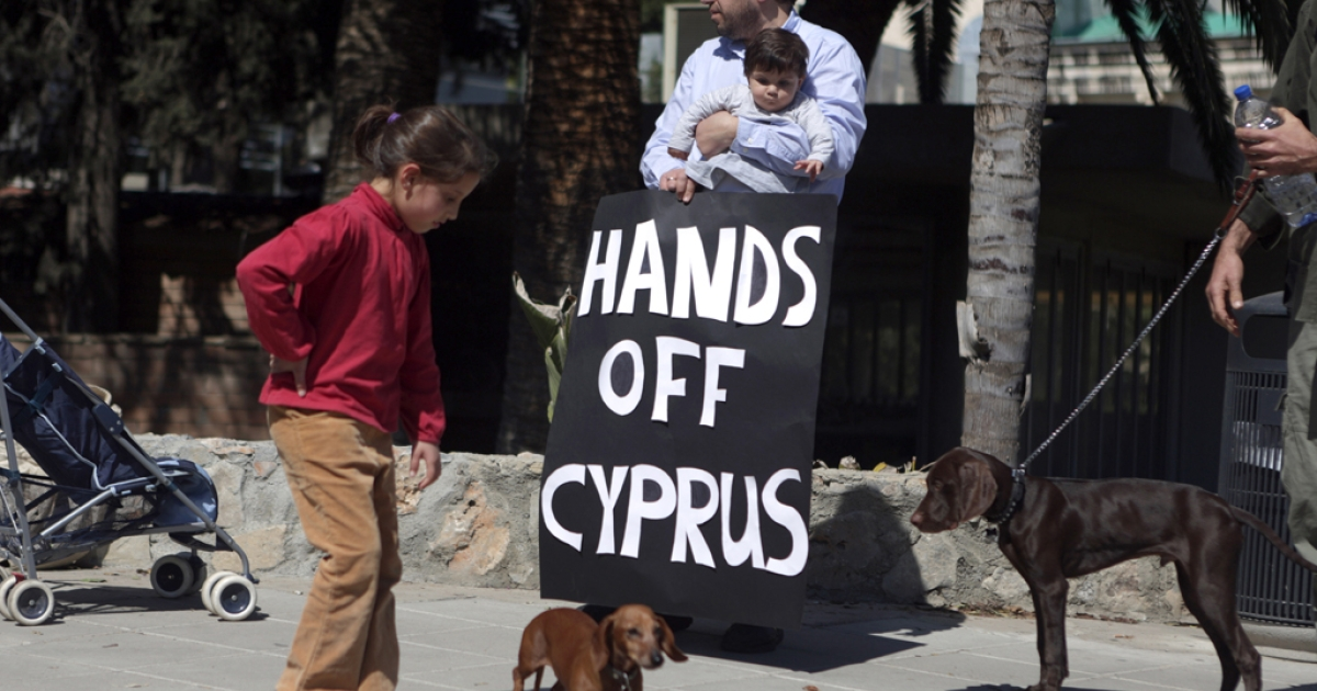 Cypriots protest outside the parliament building in Nicosia, on March 18, 2013. Cyprus President Nicos Anastasiades was seeking the backing of MPs for an EU bailout deal that slaps a levy on bank savings under harsh terms that have jolted global markets and raised fears of a new eurozone debt crisis.</p>