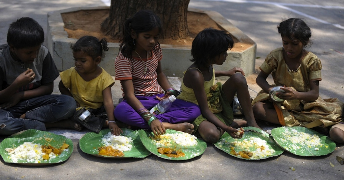 Indian homeless eat food at a feeding program for the poor in Hyderabad on March 17, 2013. India still has the world's largest number of impoverished in a single country, of its nearly one billion inhabitants, an estimated 350-400 million live below the poverty line with 75 percent of them in the rural areas.</p>