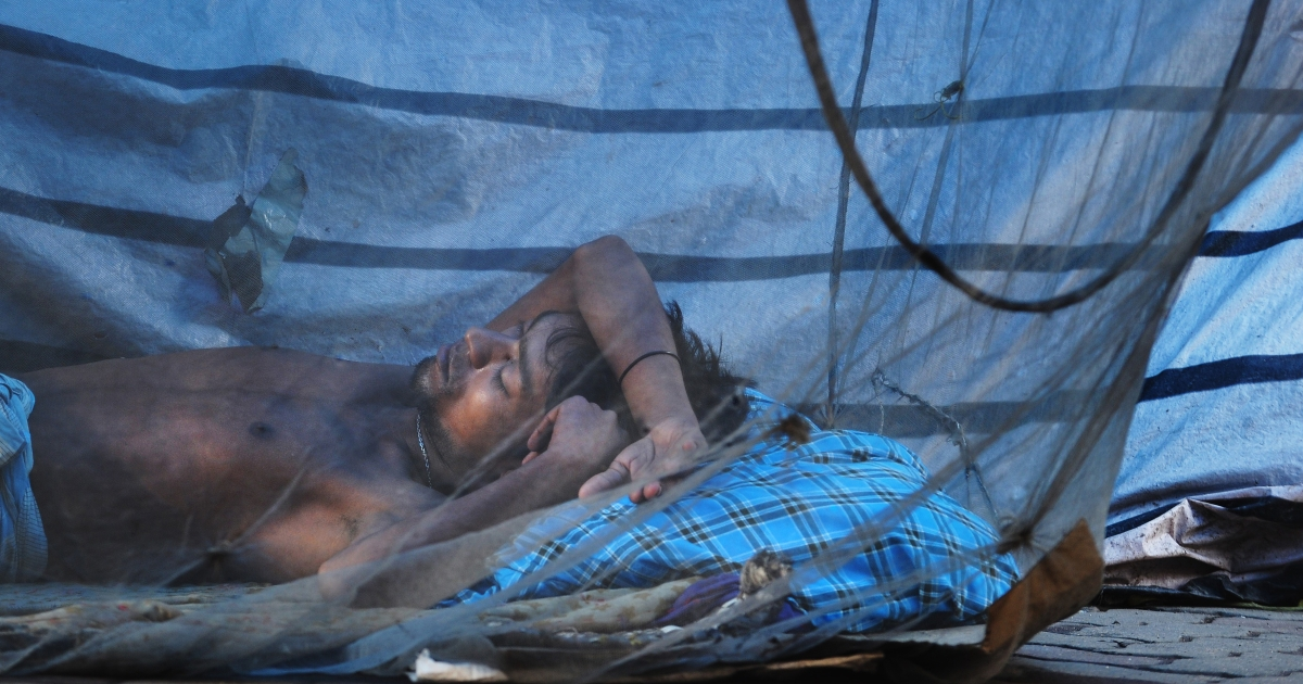 An Indian labourer takes a nap under a mosquito net on the pavement in Kolkata on August 10, 2012.</p>