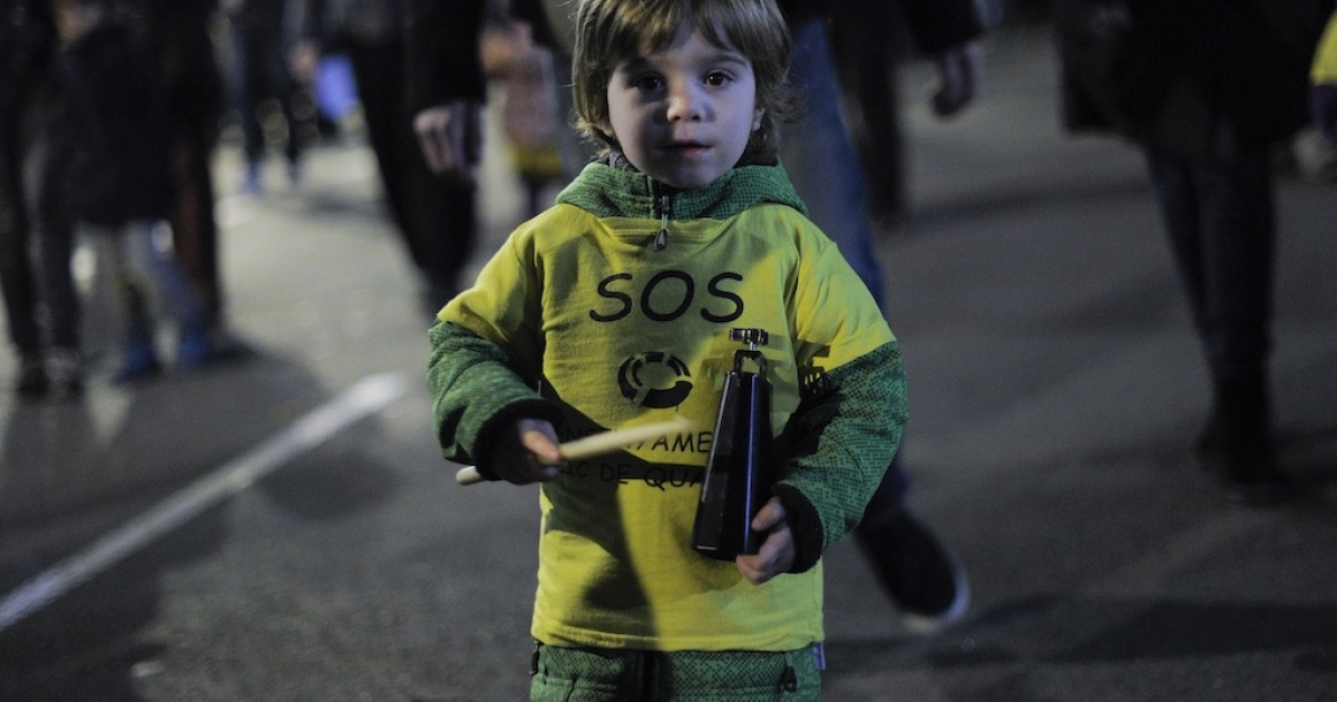 A young child attends a protest against government's plans to reform the use of Catalan language and cuts in the center of Barcelona on December 13, 2012.  (JOSEP LAGO/AFP/Getty Images)</p>