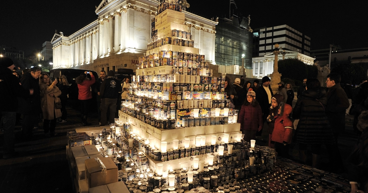 Children in Athens look at a Christmas tree made of milk tin cans, after donating some on December 14, 2012, during an event organized by Medecins du Monde, a non-governmental humanitarian aid organisation. Child poverty has been skyrocketing in the debt-ridden country.</p>