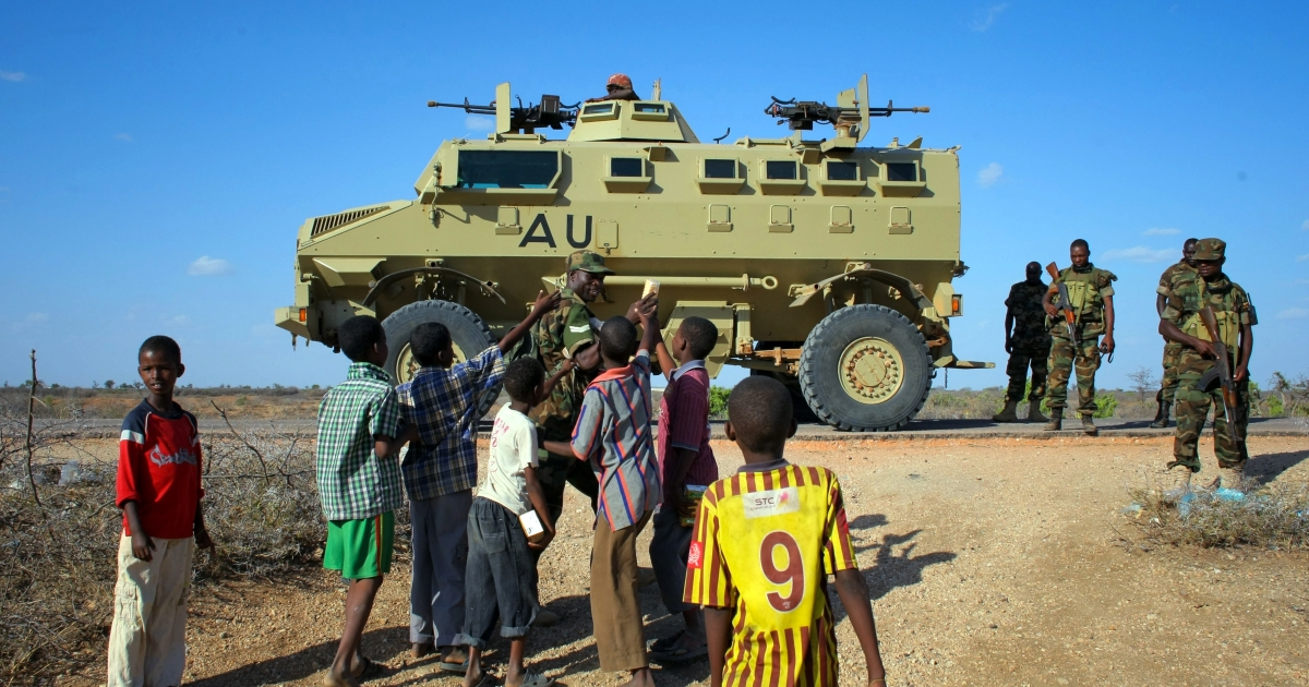 A handout picture taken and released by the African Union-United Nations Information Support team on February 28, 2013 shows a Ugandan soldier serving with the African Union Mission in Somalia (AMISOM) handing out biscuits to young Somali children.</p>