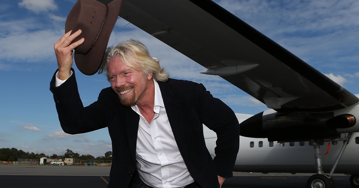 Sir Richard Branson tips his hat on the tarmac at Perth Airport on May 7, 2013 in Perth, Australia.</p>