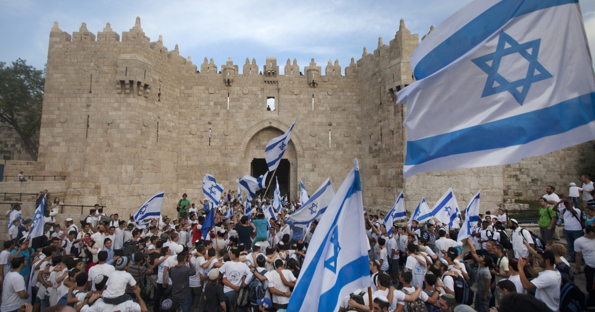 Israeli youths hold their national flag as they take part in the 'flag march' through Damascus Gate in Jerusalem's old city during celebrations for Jerusalem Day on May 8, 2013 which marks the anniversary of the 'reunification' of the holy city after Israel captured the Arab eastern sector from Jordan during the 1967 Six-Day War.</p>