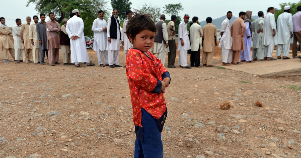 A young Pakistani child plays in front of a queue of voters outside a polling station in Islamabad on May 11, 2013.</p>