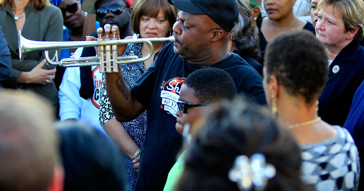 Kenneth Terry with the Treme Brass Band plays the trumpet on the cornor of North Villere and Frenchmen Street during a community response to a shooting during a Mother's Day parade, on May 13, 2013 in New Orleans, Louisiana. Nineteen people were injured during the shooting, including two children.</p>