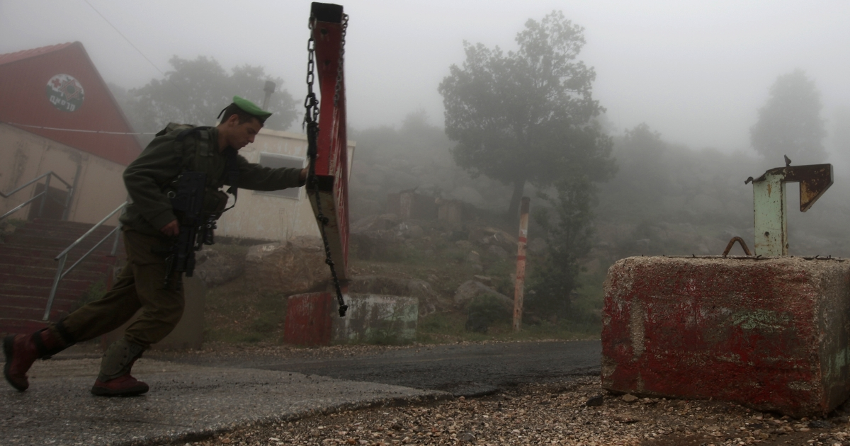 An Israeli soldier partially closes a barrier across a road, on Mount Hermon in the northern Israel occupied Golan Heights on May 15, 2013, after two projectiles fired from Syria hit Mount Hermon.</p>