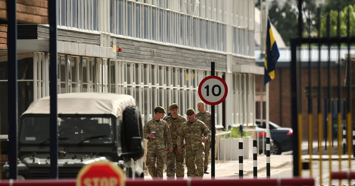 Soldiers walk past a flag which flies at half mast inside Woolwich Barracks on May 23, 2013 in London, England. A British soldier was murdered by suspected Islamists near London's Woolwich Army Barracks yesterday in a savage machete attack.</p>