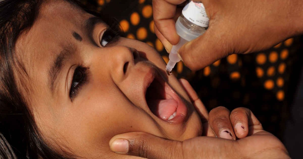 An Indian medical volunteer administers a dose of oral vaccine to a child during a national immunisation programme in Hyderabad on February 19, 2012.</p>