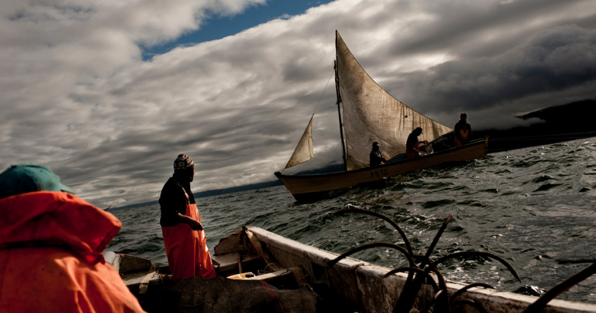 In the foreground, Don Daniel Quinan with his son Ramiro, grandson Gonzalo, and a recently caught 7 kilo Chilean croaker, sail by the boat of Miguel Barrientos, president of the Bonifacio Fishermen's Union.</p>