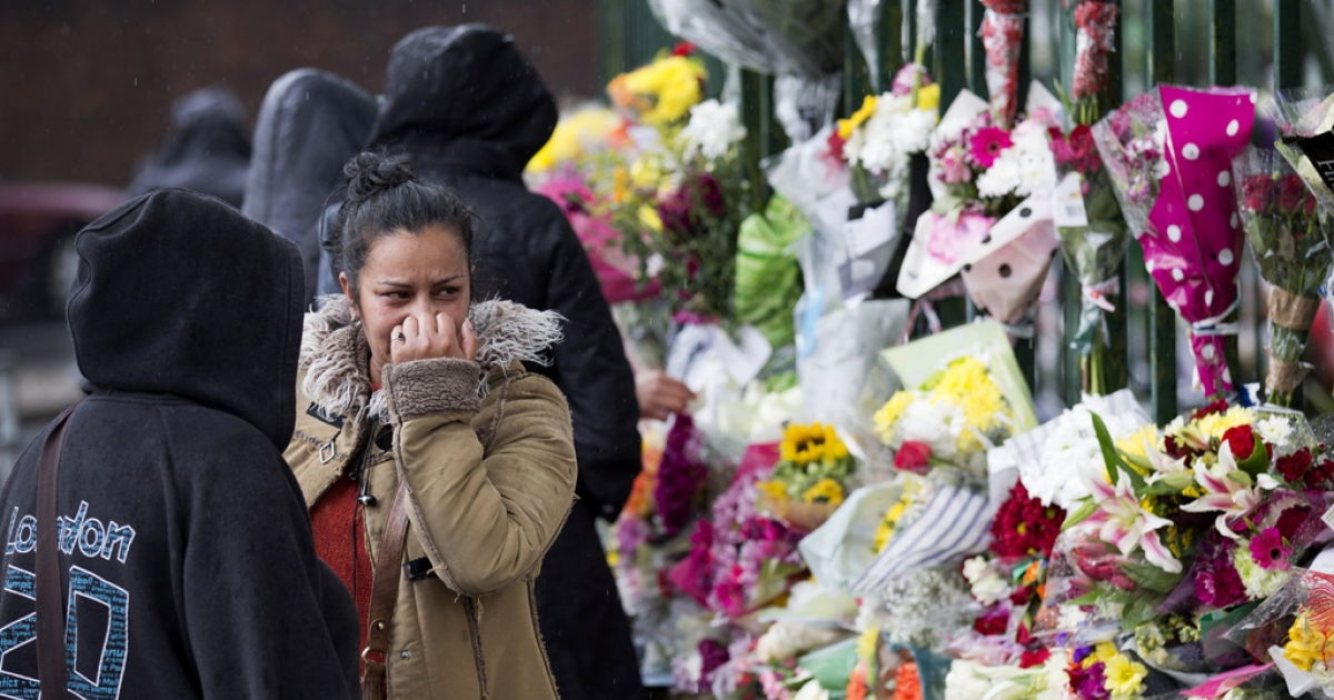 A woman reacts as she looks at floral tributes left at the scene where Drummer Lee Rigby of the 2nd Battalion was killed outside Woolwich Barracks in London on May 24, 2013.</p>
