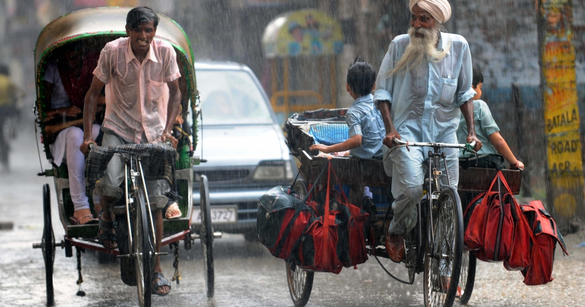 Indian commuters make their way during a downpour in Amritsar on July 27, 2009. NASA scientists claim in a new study that temperate regions will experience more drought while the tropics more extreme rains in the future due to climate change.</p>