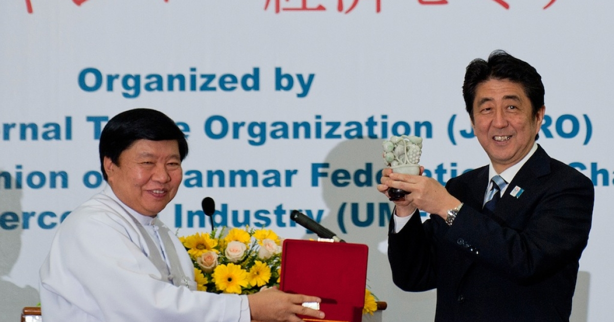 Japan's Prime Minister Shinzo Abe (R) accepts a gift from U Win Aung, chairman the Union of Myanmar Federation of Chambers of Commerce and Industry in Myanmar on May 25, 2013.</p>