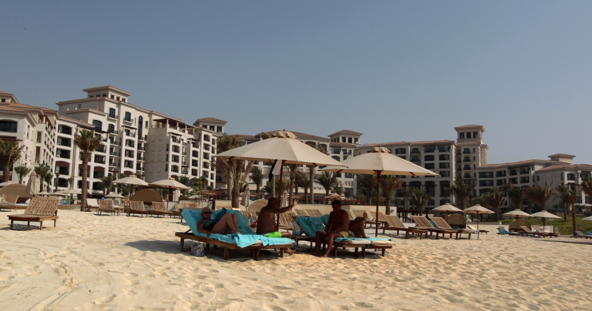 Tourists sunbath along the beach at the St. Regis hotel located in the Saadiyat district, an Island off the city of Abu Dhabi on June 7, 2012.</p>