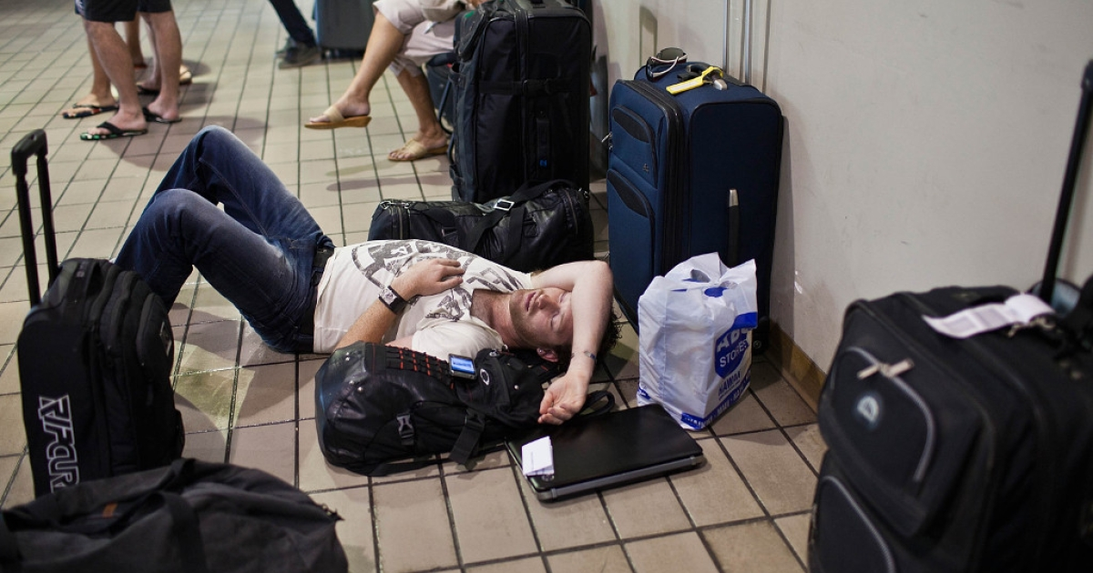A man sleeps amongst the luggage of his traveling companions near the Air Australia ticket counter at Honolulu International Airport on Thursday, Feb. 16 , 2012.</p>