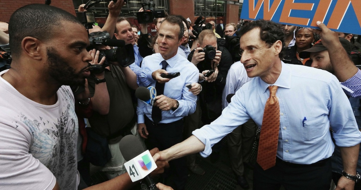Anthony Weiner greets a man while courting voters on May 23, 2013 in New York City. Weiner is vowing not to quit the race despite calls to drop out.</p>