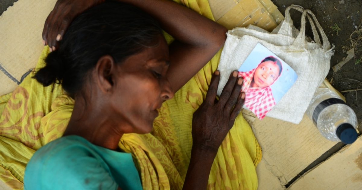 A Bangladeshi woman sleeps as she holds the portrait of her missing relative, believed to be trapped in the rubble of an eight-storey building collapse in Savar, on the outskirts of Dhaka, on May 4, 2013.</p>