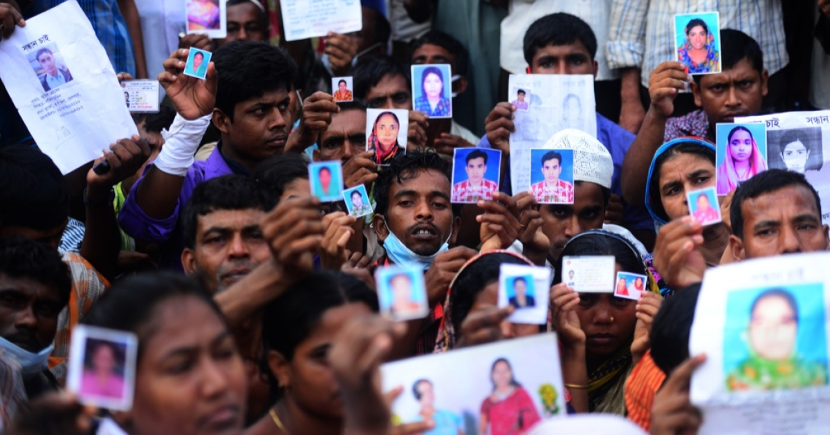 Bangladeshi relatives hold photos of the missing and dead workers three days after an eight-storey building collapsed in Savar, on the outskirts of Dhaka on April 27, 2013. The death toll from the disaster had risen above 1,000 by May 10.</p>