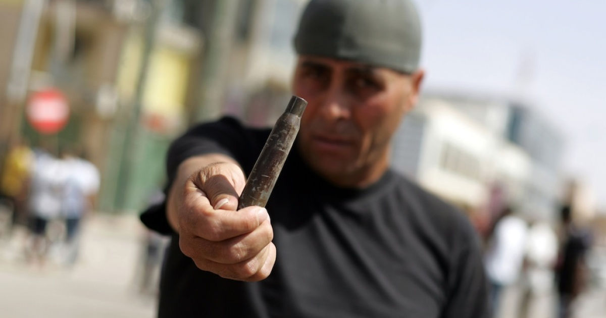 A man shows an empty bullet shell that he found outside a police station that was attacked overnight on May 15, 2013 in the Libyan eastern city of Benghazi.</p>