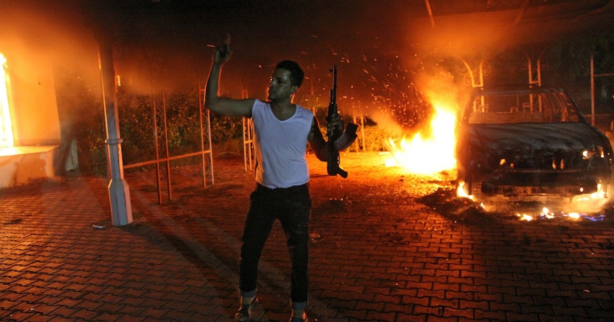 An armed man waves his rifle as buildings and cars are engulfed in flames after being set on fire inside the US consulate compound in Benghazi late on Sept. 11, 2012.</p>