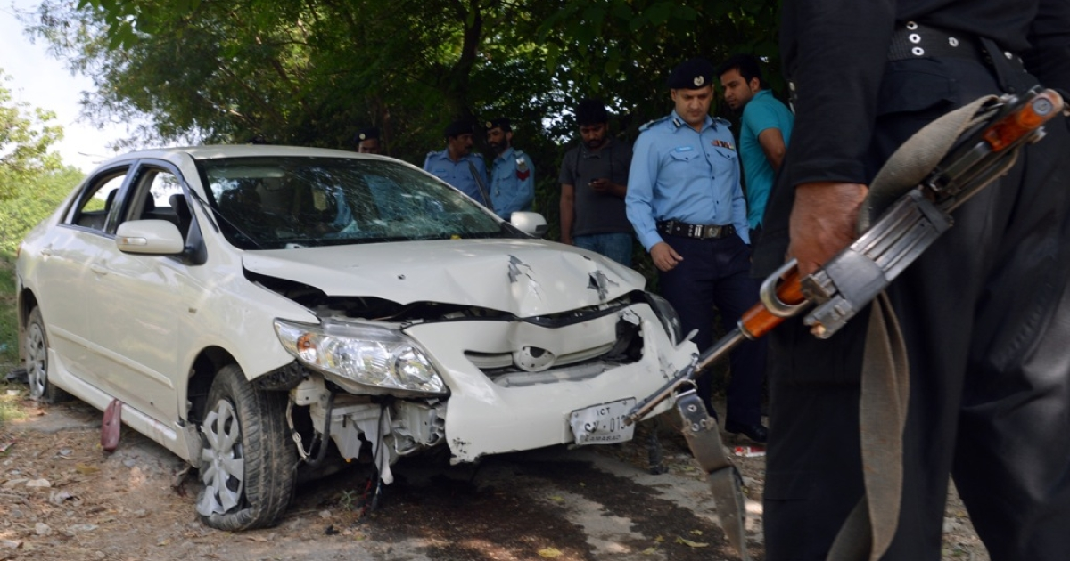 Pakistani police officials examine the bullet-riddled car of a slain government prosecutor Chaudhry Zulfiqar after an attack by gunmen in Islamabad on May 3, 2013. Pakistan's main government prosecutor on the Benazir Bhutto murder case was shot dead in Islamabad en route to court, police said.</p>