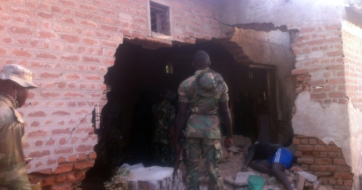 A soldier stands in front of a damaged wall and the body of a prison officer killed during an attack on a prison in the northeastern town of Bama, on May 7, 2013. Nigerian gunmen on May 7, 2013 launched coordinated attacks on military barracks, a prison and police stations killing 55 people and springing 105 inmates, the army said. 'Heavily armed Boko Haram terrorists' launched the attacks around 5:00 am.</p>