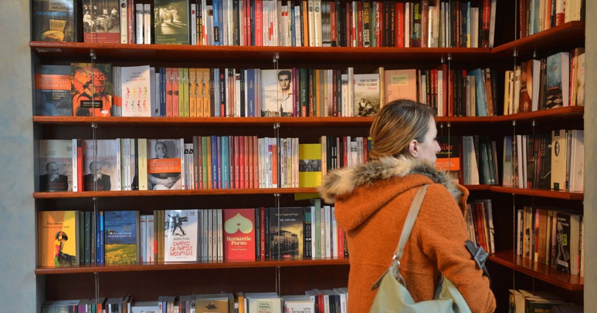 A woman looks at the contemporary Romanian literature bookshelf at a library in Bucharest.</p>