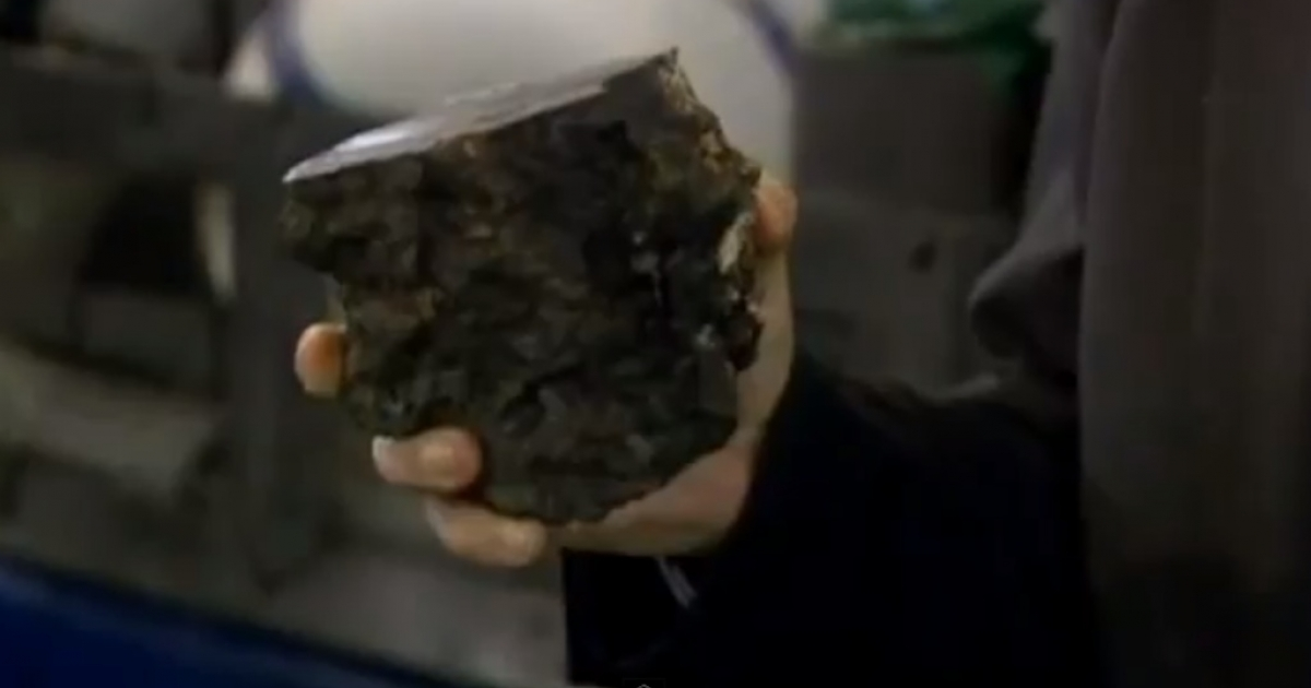 A scientist holds up a piece of granite found 8,000 feet undersea off the coast of Rio, where they think they have discovered the Brazilian