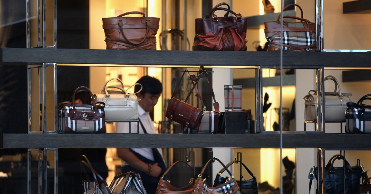 A Chinese man walks into the Burberry flagship store on June 11, 2012 in Beijing.</p>