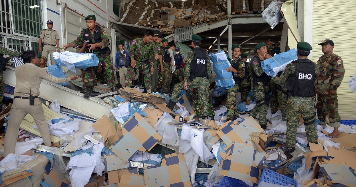 Cambodian soldiers move debris after a factory collapsed in Kampong Speu province on May 16, 2013.</p>