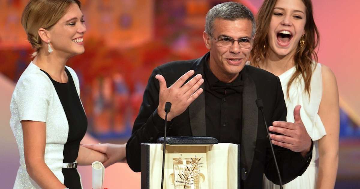 French-Tunisian director Abdellatif Kechiche (C) speaks on stage on May 26, 2013 flanked by French actresses Lea Seydoux (L) and Adele Exarchopoulos after he was awarded with the Palme d'Or for the film