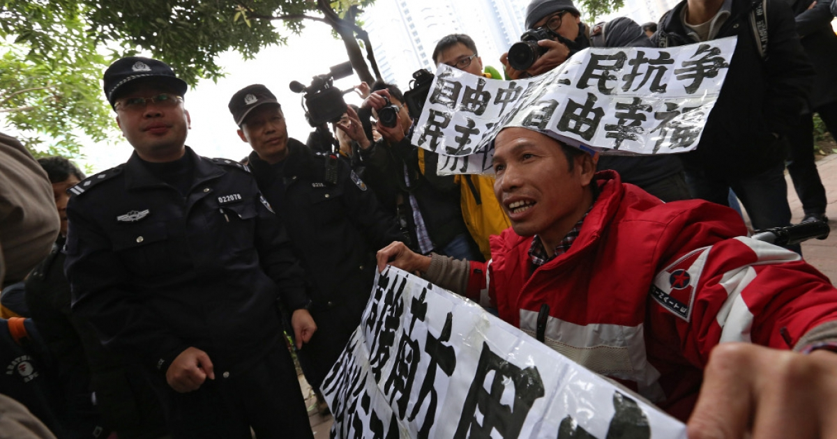 Police look on as a man protests as a group of people calls for greater media freedom outside the headquarters of Nanfang Media Group in Guangzhou on Jan. 9, 2013.</p>