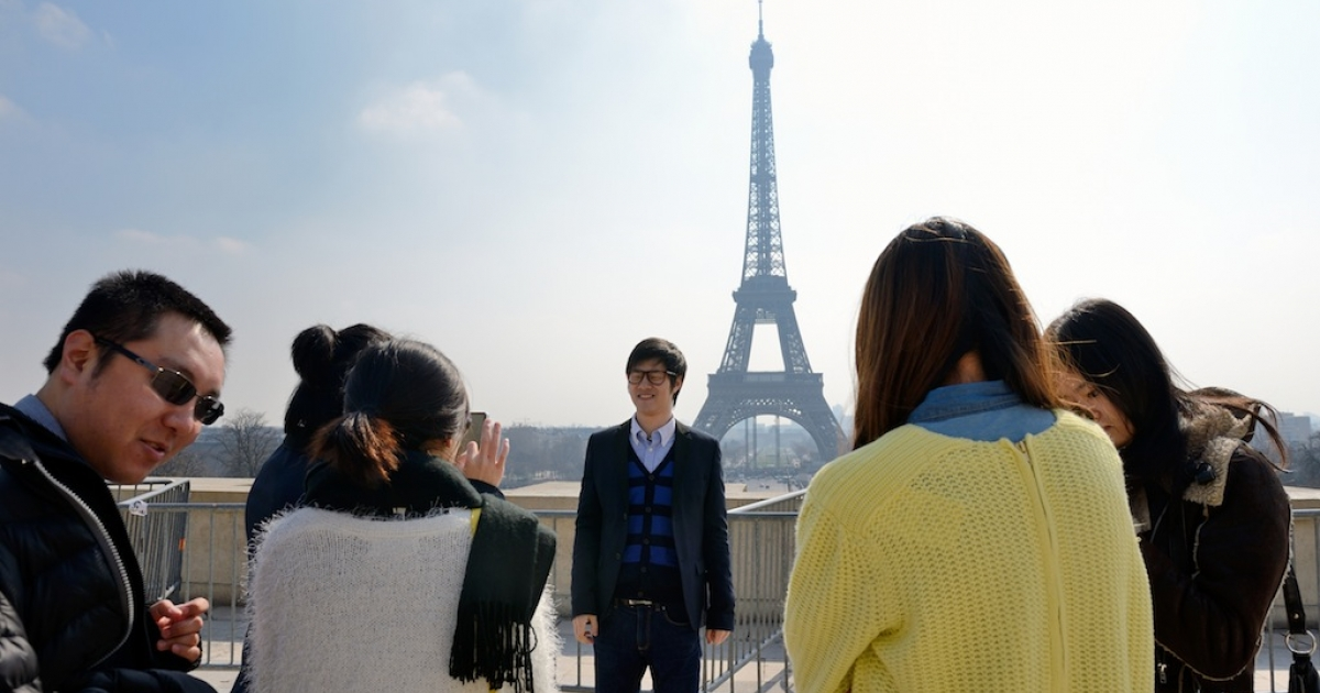 Chinese tourist take souvenir pictures in front of of the Eiffel tower on March 27, 2013 in Paris.</p>