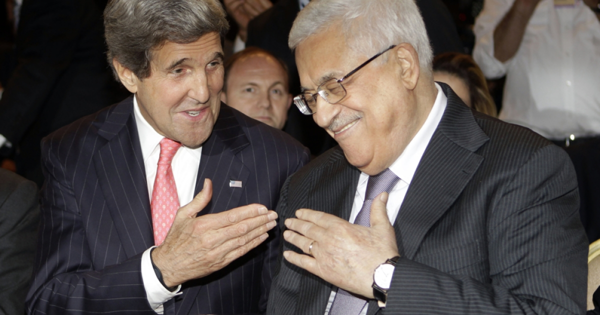 U.S. Secretary of State John Kerry (L) speaks with Palestinian President Mahmud Abbas at the World Economic Forum on the Middle East and North Africa at the Dead Sea on May 26, 2013.</p>