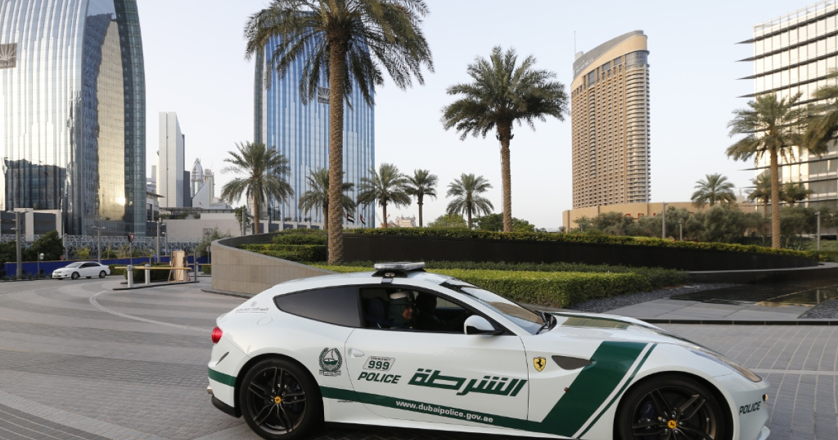 Emirati police officers drive a Ferrari police vehicle in the Gulf emirate of Dubai on April 25, 2013.</p>